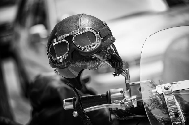 Vintage style motorbike helmet with goggles on the motorcycle handlebar. In Black and White royalty free stock photos