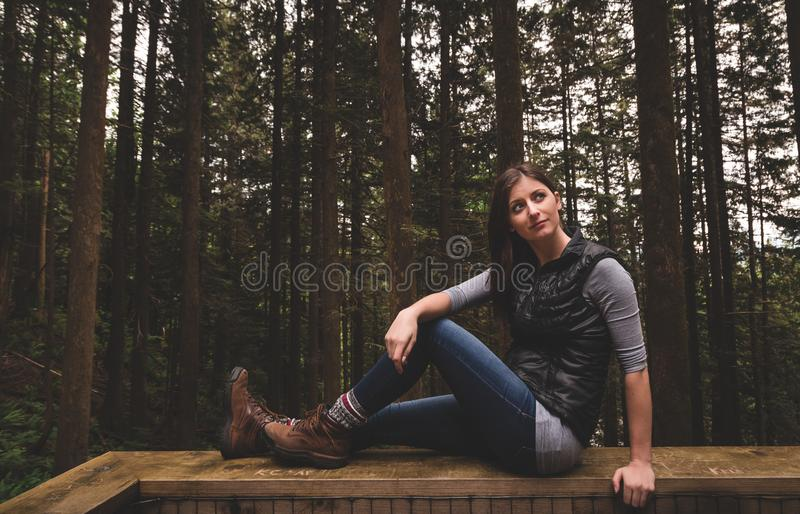 Vintage style photo of a young woman in hiking boots sitting on a railing in the forest. stock images