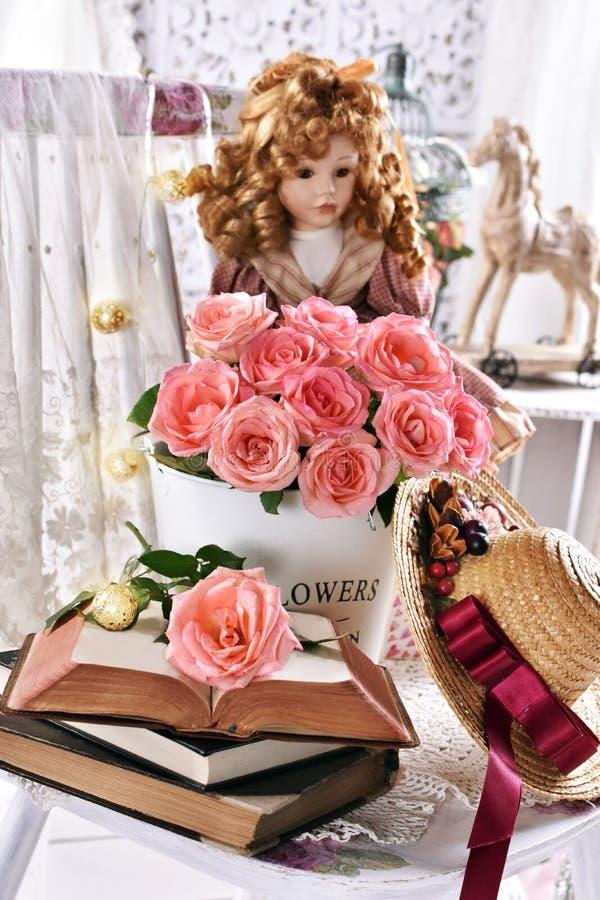 Vintage style picture met stelletje roze rozen boeken en een pop stock foto