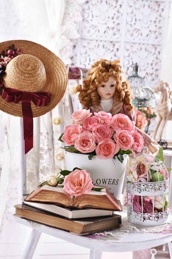 Vintage style picture met stelletje roze rozen boeken en een pop royalty-vrije stock afbeeldingen