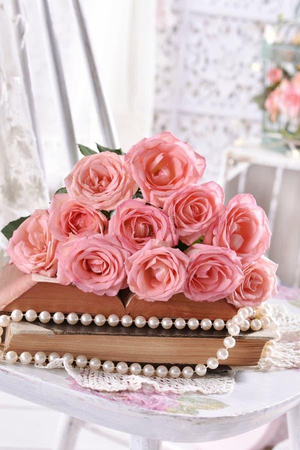 Vintage style picture met stelletje roze rozen op boeken stock foto's