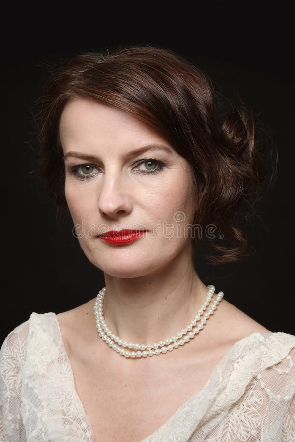 Vintage style portrait of beautiful mature woman with red lipstick royalty free stock photography