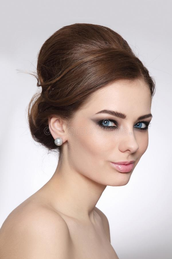 Vintage style portrait of beautiful woman with fancy hair bun and smoky eye makeup stock images