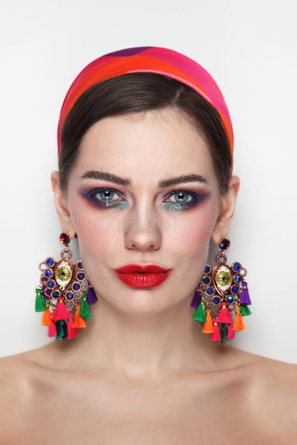 Vintage style portrait of beautiful woman with red lips and fancy massive earrings stock image