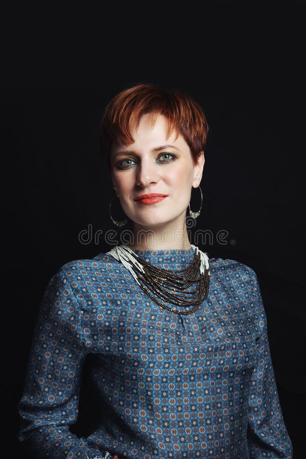 Vintage style portrait of beautiful red-haired woman with fancy makeup royalty free stock photo