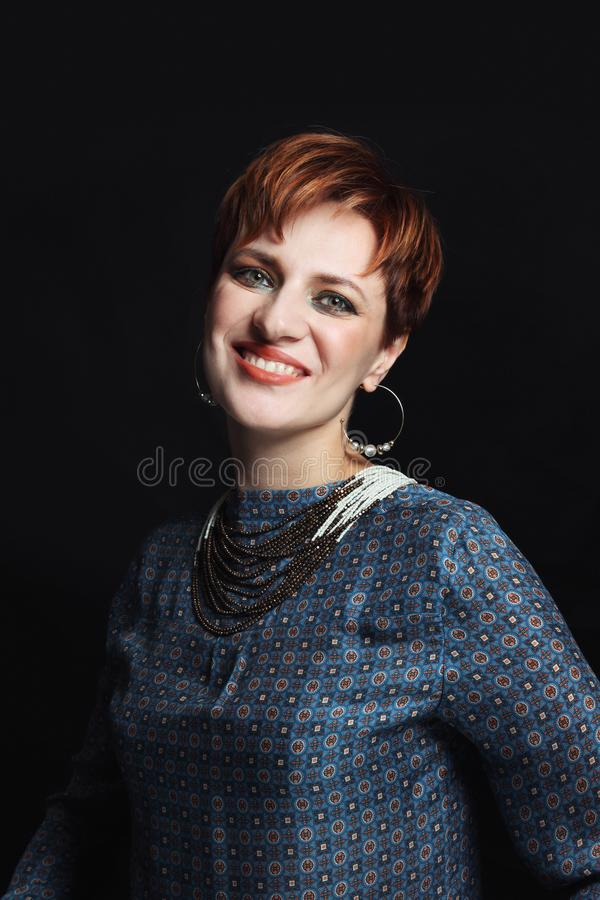 Vintage style portrait of young beautiful smiling red-haired woman with fancy makeup royalty free stock photography