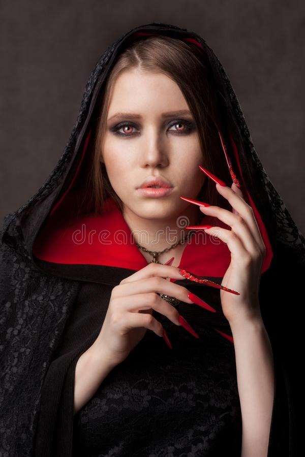 Vintage style portrait of young beautiful vampire woman with gothic Halloween makeup. Manicured red stilettos nails royalty free stock photography