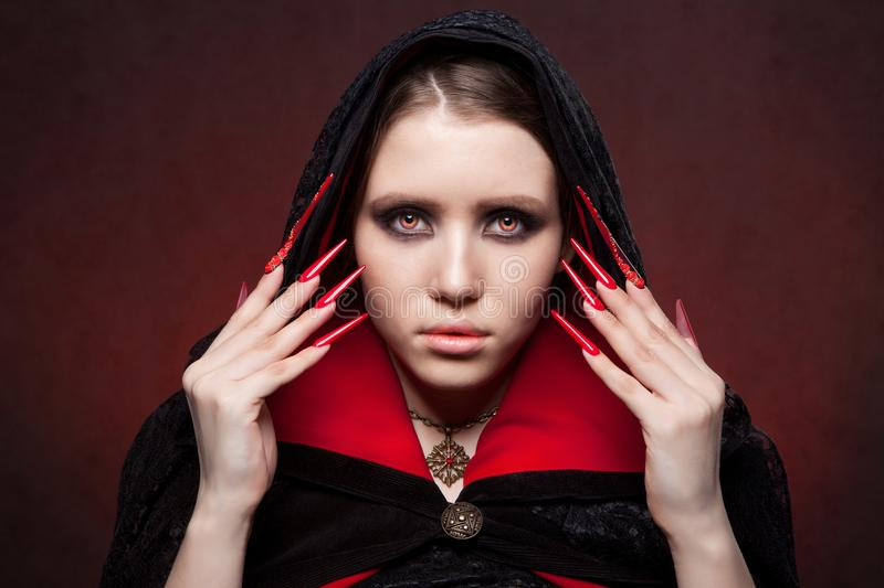 Vintage style portrait of young beautiful vampire woman with gothic Halloween makeup. Manicured red stilettos nails stock photos