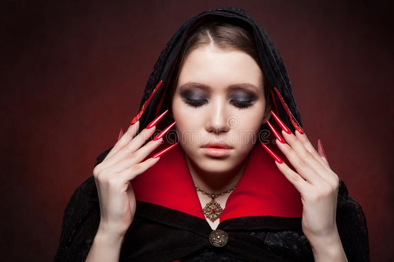 Vintage style portrait of young beautiful vampire woman with gothic Halloween makeup. Manicured red stilettos nails stock photo
