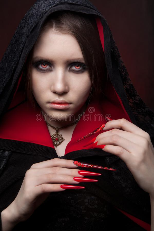 Vintage style portrait of young beautiful vampire woman with gothic Halloween makeup. Manicured red stilettos nails royalty free stock images