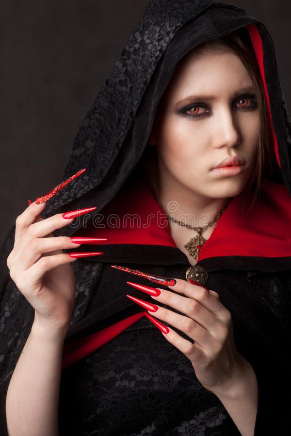 Vintage style portrait of young beautiful vampire woman with gothic Halloween makeup. Manicured red stilettos nails stock images