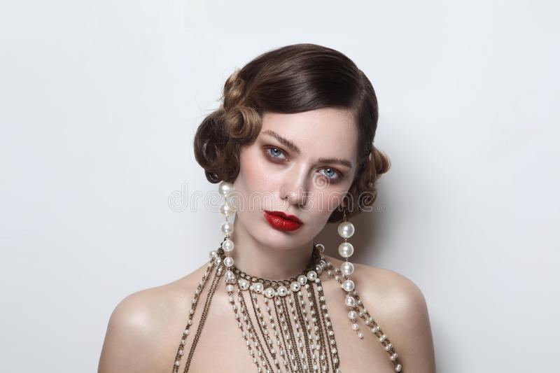 Vintage style portrait of beautiful woman with fancy pearl earrings and necklace stock images