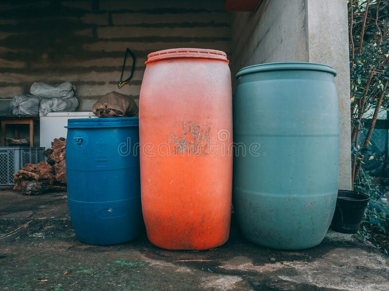 Vintage-style shot of metal containers of different colors in an unfinished building in a backyard. A vintage-style shot of metal containers of different colors royalty free stock image