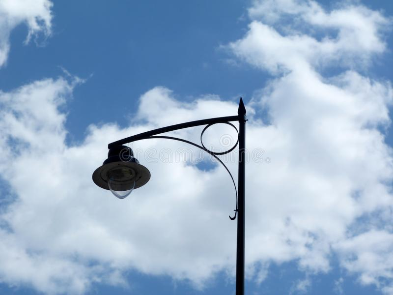 Vintage style street lamp detail under blue sky and white clouds in low angle perspective. View in Budapest, Hungary. retro style technology royalty free stock photos