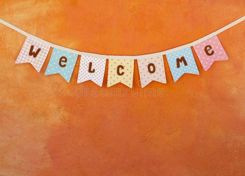 Vintage style welcome party flag design on orange cement wall stock photos