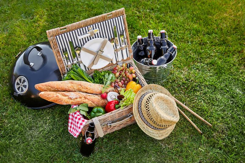 Vintage style wicker picnic hamper. With an assortment of fresh vegetables for salads and crusty French baguettes alongside a silver cooler with bottles of beer stock photos