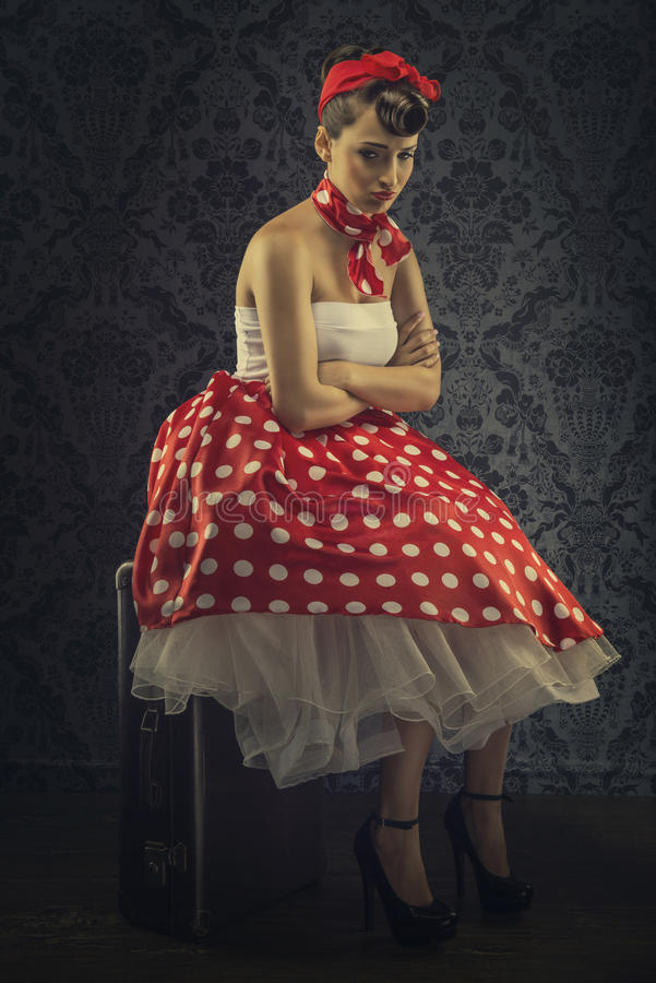 Vintage style - Woman sitting in the room with red polka dot dress.  stock image