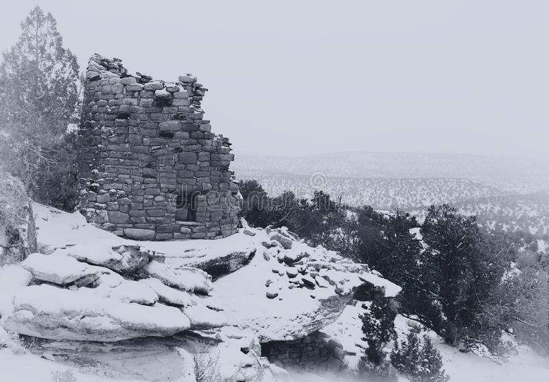 A vintage styled B&W photo an Anasazi ruin. Painted Hand Tower, an Anasazi ruin, overlooking Hovenweep Canyon during a snow storm. A black and white photograph stock photography