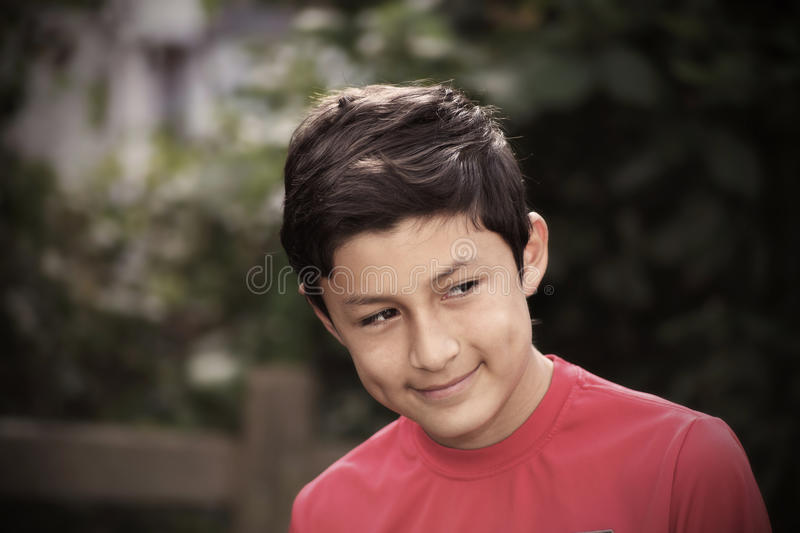 Vintage stylistic portrait of smiling boy. With de-saturated look and vignetting - shot with vintage lens stock photography