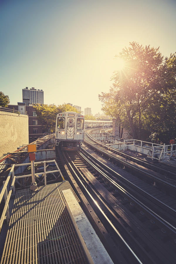 Vintage stylized train entering platform against rising sun in C. Hicago city, USA royalty free stock image
