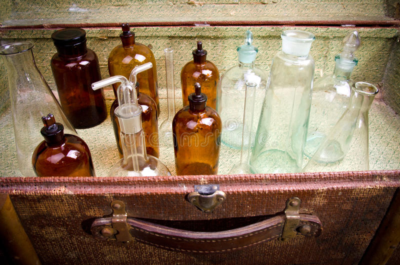 Vintage suitcase with chemical flasks and banks stock images