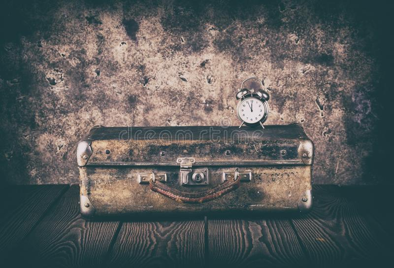 Vintage suitcase and a clock on a wooden floor royalty free stock photo