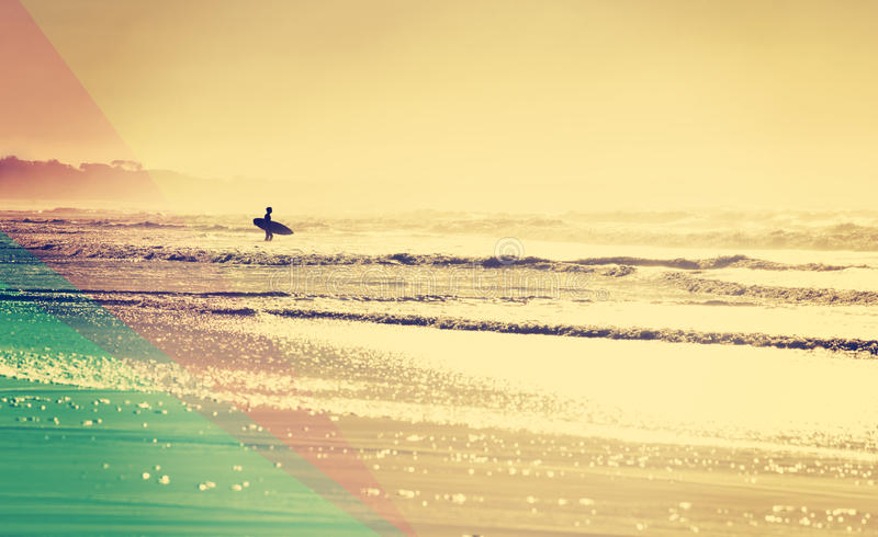 Vintage summer beach with surfer in the water royalty free stock photography