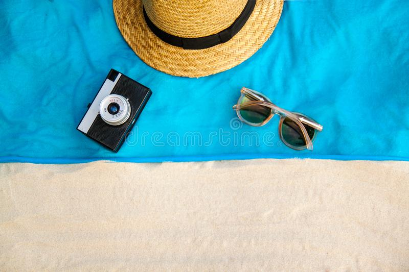 Vintage summer wicker straw beach bag, sun glasses, hat cover-up beachwear wrap on the sand, tropical background stock image