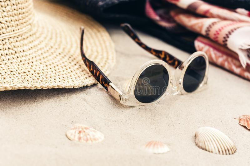 Vintage summer wicker straw beach bag, sun glasses, hat, cover-up beachwear wrap on the sand, tropical background.  stock photos