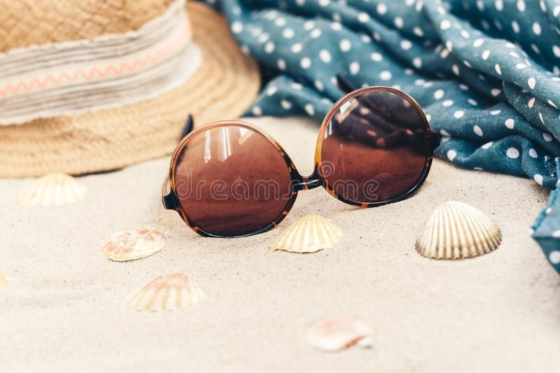 Vintage summer wicker straw beach bag, sun glasses, hat, cover-up beachwear wrap on the sand, tropical background.  royalty free stock photography