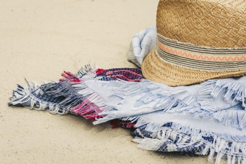 Vintage summer wicker straw beach hat and blue pareo on the seashore of Catania, Sicily, Italy.  royalty free stock photo