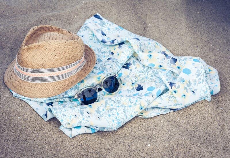 Vintage summer wicker straw beach hat, pareo and sunglasses on the seashore of Catania, Sicily, Italy.  royalty free stock photography
