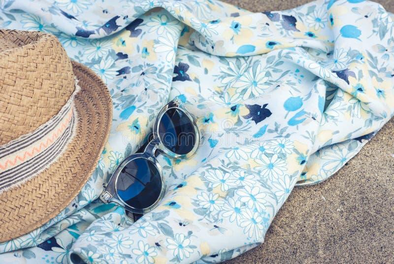 Vintage summer wicker straw beach hat, pareo and sunglasses on the seashore of Catania, Sicily, Italy.  stock photography