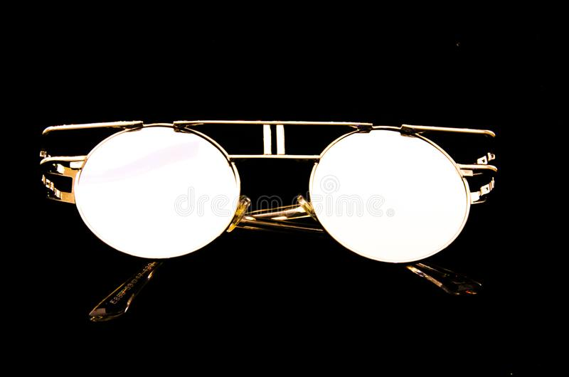 Vintage sun glasses, contrasted on the black background. Vintage sun glasses, made from metal, contrasted on the white background, fashion. Round glasses, metal stock photography