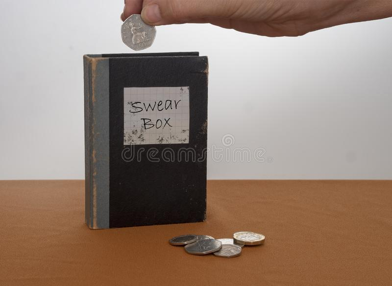 Vintage swear box, with UK coins, money and hand. Vintage swear box with UK coins, money and hand royalty free stock image