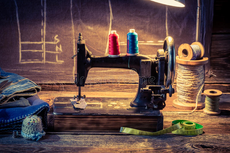 Vintage tailor workshop with sewing machine, cloth and scissors stock illustration