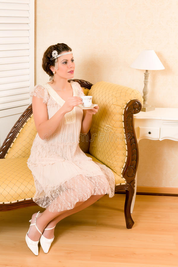 Vintage tea party. Attractive vintage 1920s woman sitting on a chaise longue royalty free stock images