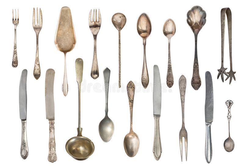 Vintage tea spoons, forks, sugar tongs, cake spatula, knives isolated on white background. Antique silverware. Retro royalty free stock photos