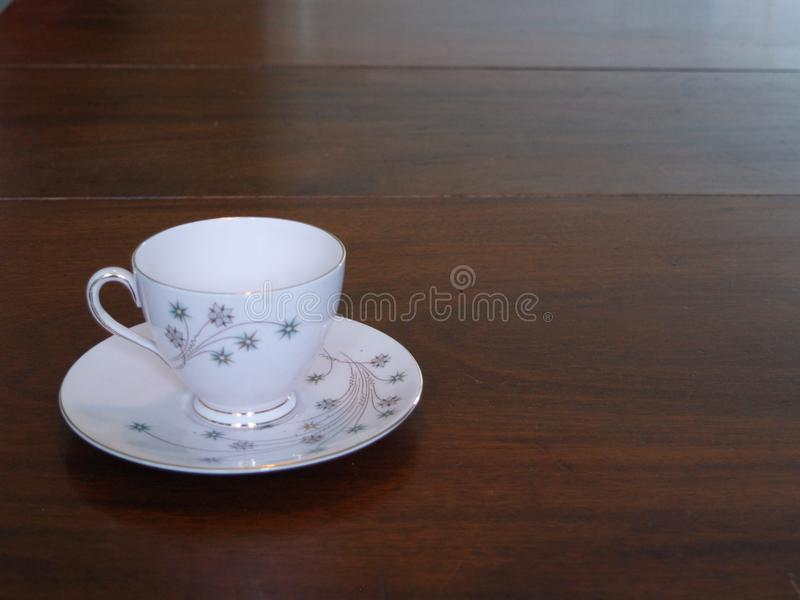 Vintage teacup on mahogany dining table. Vintage bone china teacup and saucer in pink with gilt decoration royalty free stock image