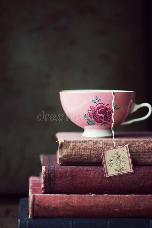 Vintage teacup on stack of old books stock photos