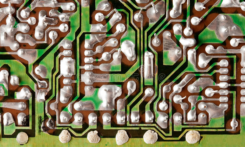 Vintage technology concept with circuit board close-up. Green electronic chip soldering paths and trace. Shallow depth. Of field photo stock images