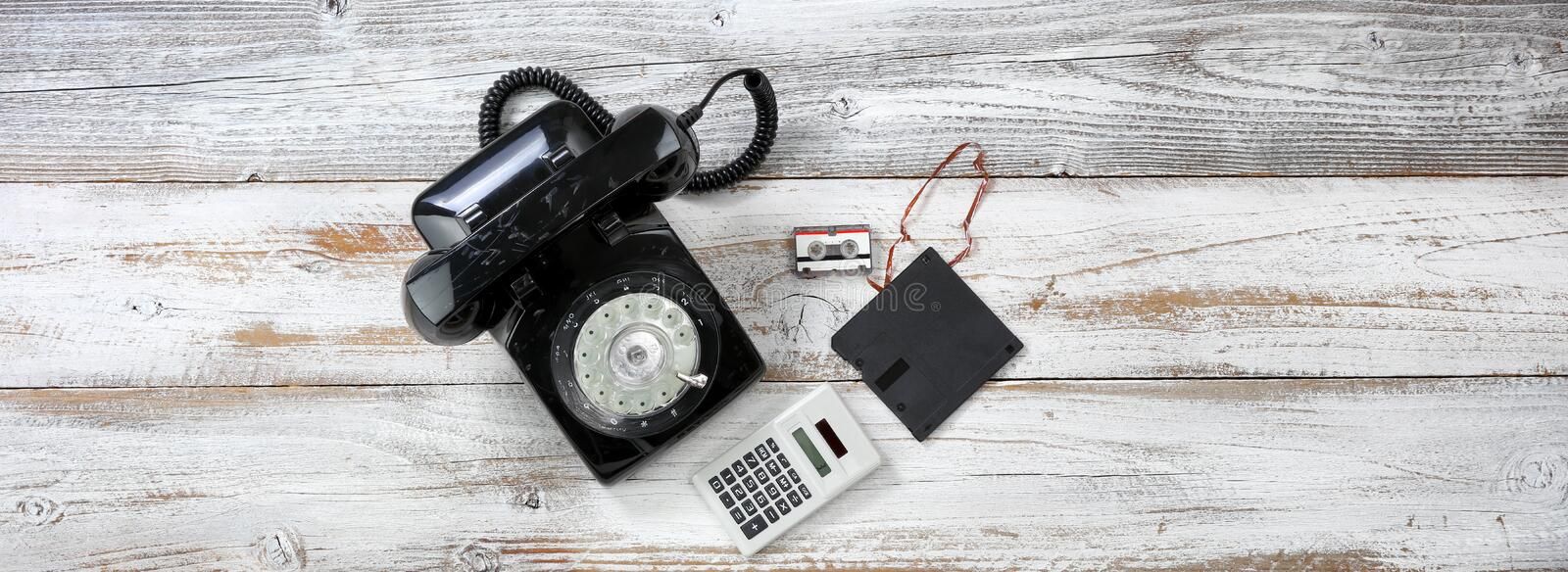 Vintage technology includes rotary dial phone and old data disk and tape storage devices. Vintage technology includes rotary dial phone and old data storage stock photo