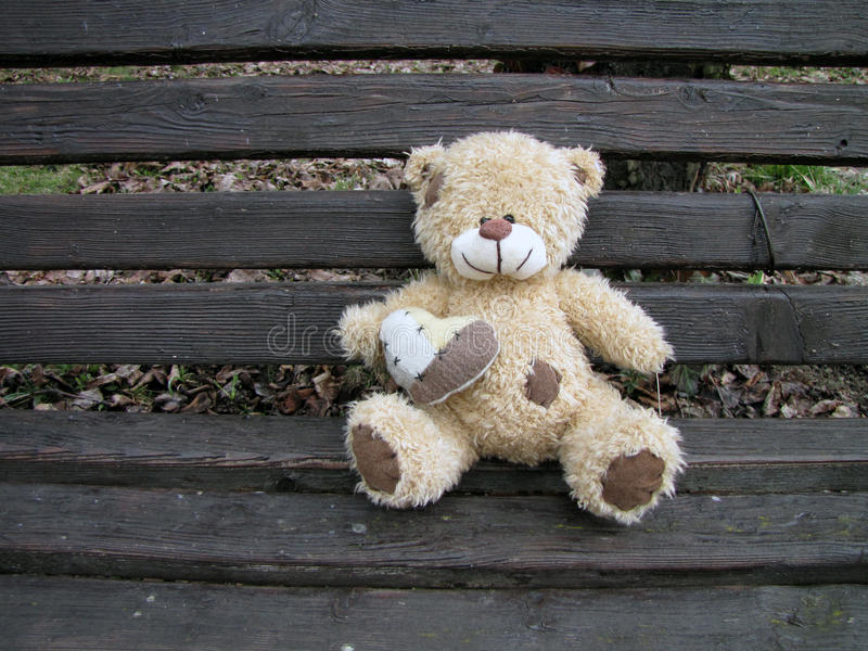 Vintage teddy bear holding heart and sitting on the wooden bench stock images
