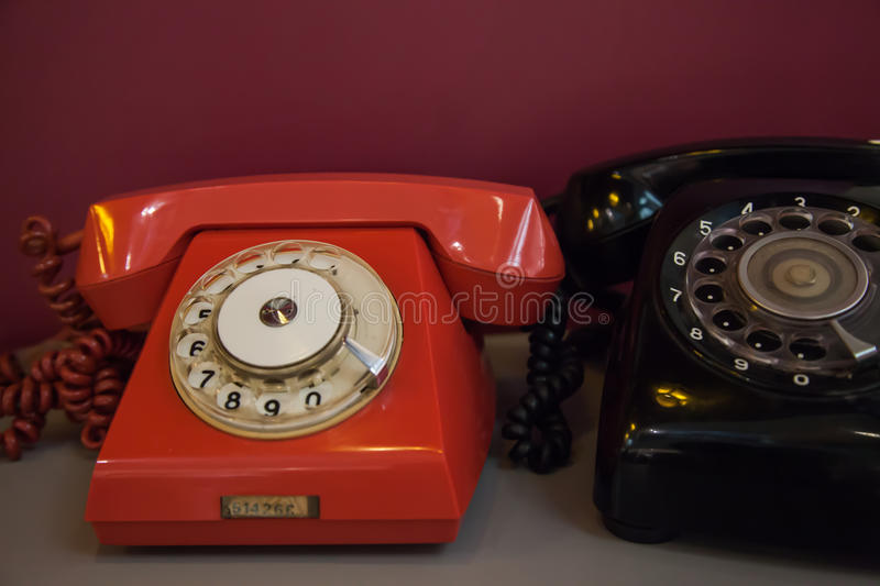 Vintage telephone antique technology; red and black old objects. royalty free stock images