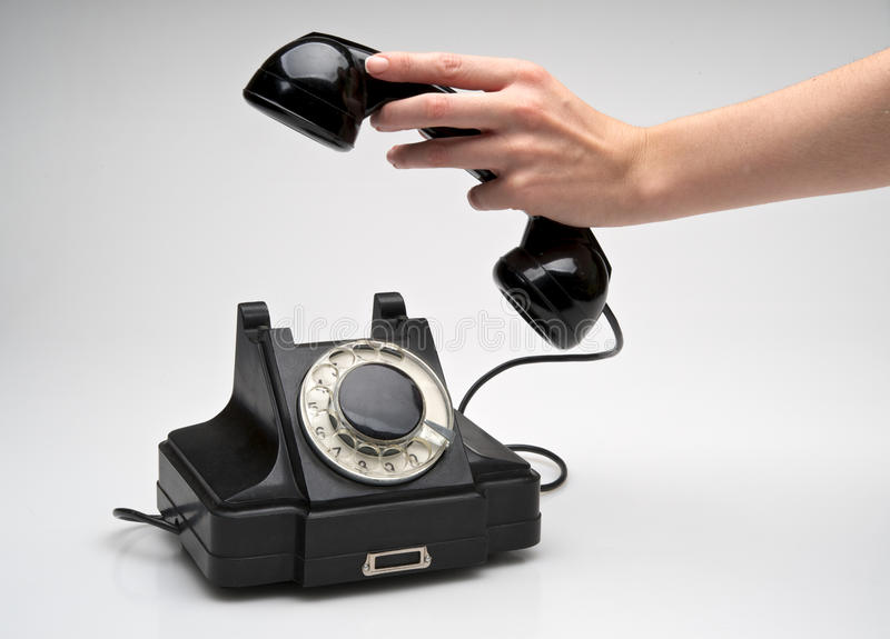 Vintage telephone being picked up stock photo