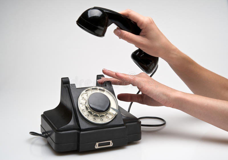 Vintage telephone being picked up stock images