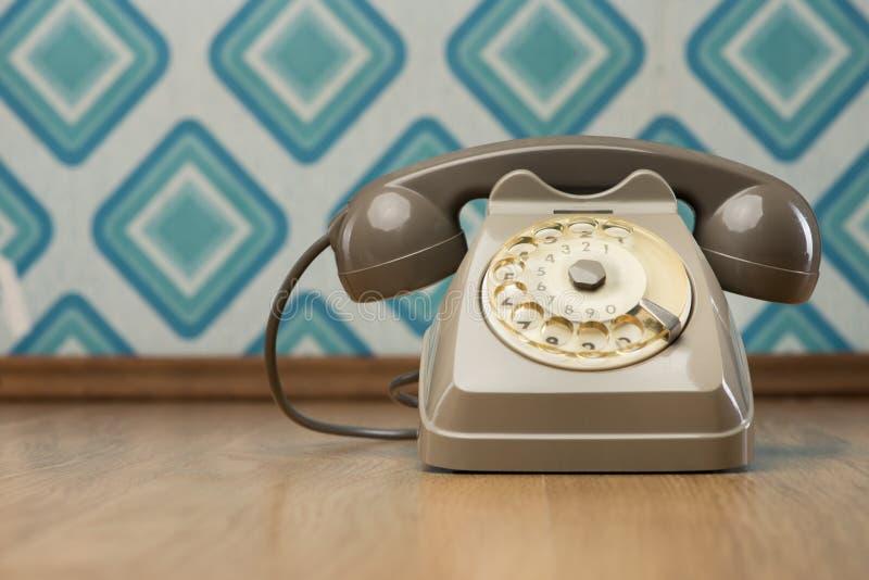 Vintage telephone on diamond wallpaper. Vintage gray telephone on hardwood floor, diamond light blue retro wallpaper on background royalty free stock images
