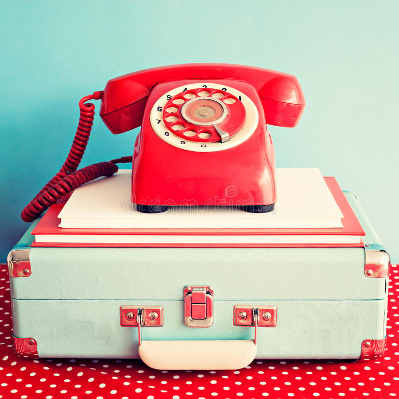 Vintage telephone over books and suitcase stock images