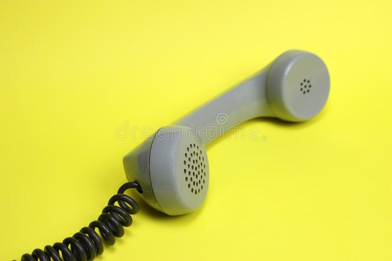 Vintage telephone receiver and cord on yellow background.  stock photography