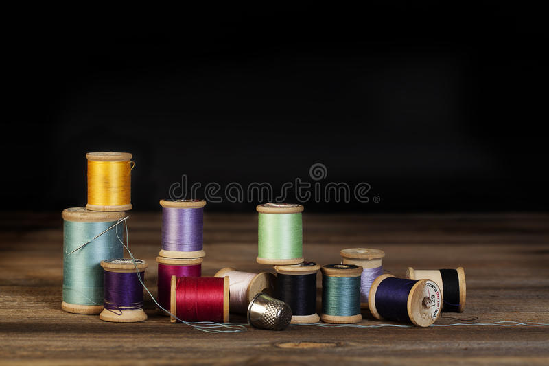 Vintage Thread Spools. Vintage wooden spools of sewing thread in various colors on wood surface with black background stock photos